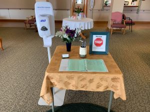 Photo of table and hand sanitizer and guest book