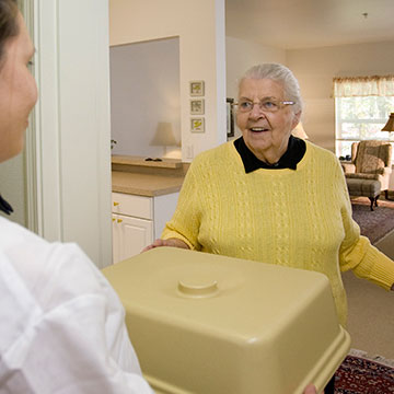 A happy resident receiving her meal in her room at Colonial Inn Olympia