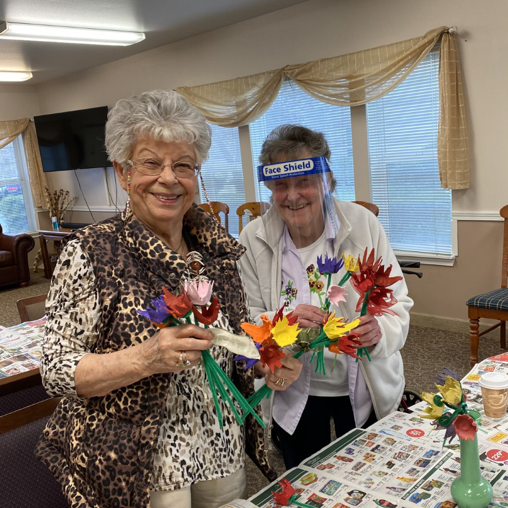 Two residents making paper tulips at Colonial Inn Olympia
