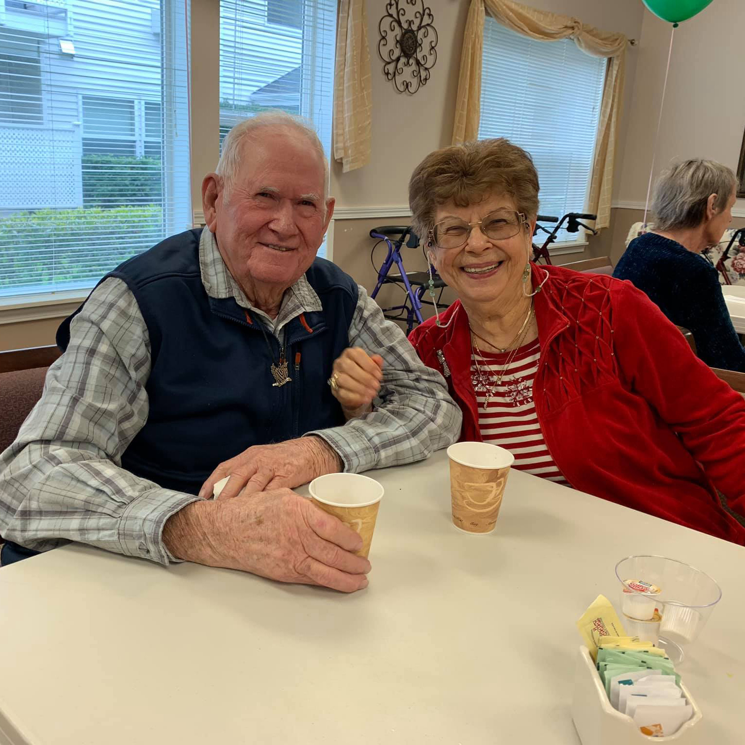Two residents sitting at a table sharing coffee at Colonial Inn Olympia
