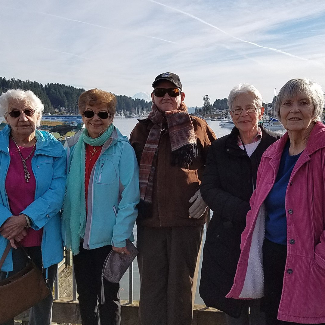 Five residents standing with their backs against the water on a wharf.