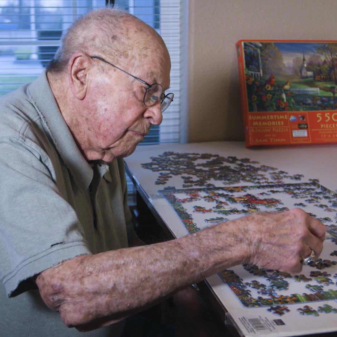 A handsome resident working on a puzzle at Colonial Inn Olympia